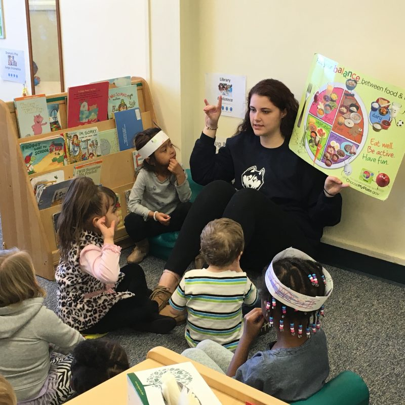 Husky Reads Student with Children
